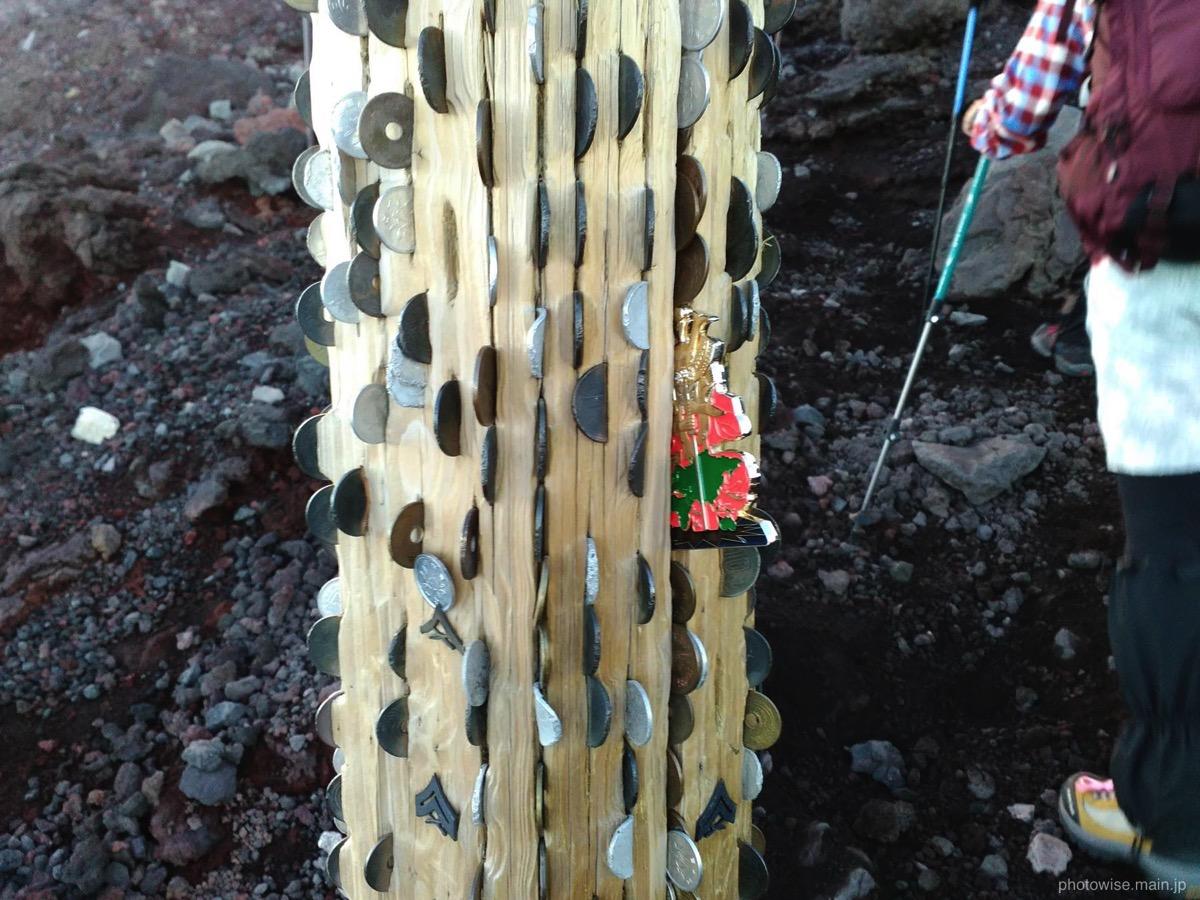 コインが埋め込まれた木の棒